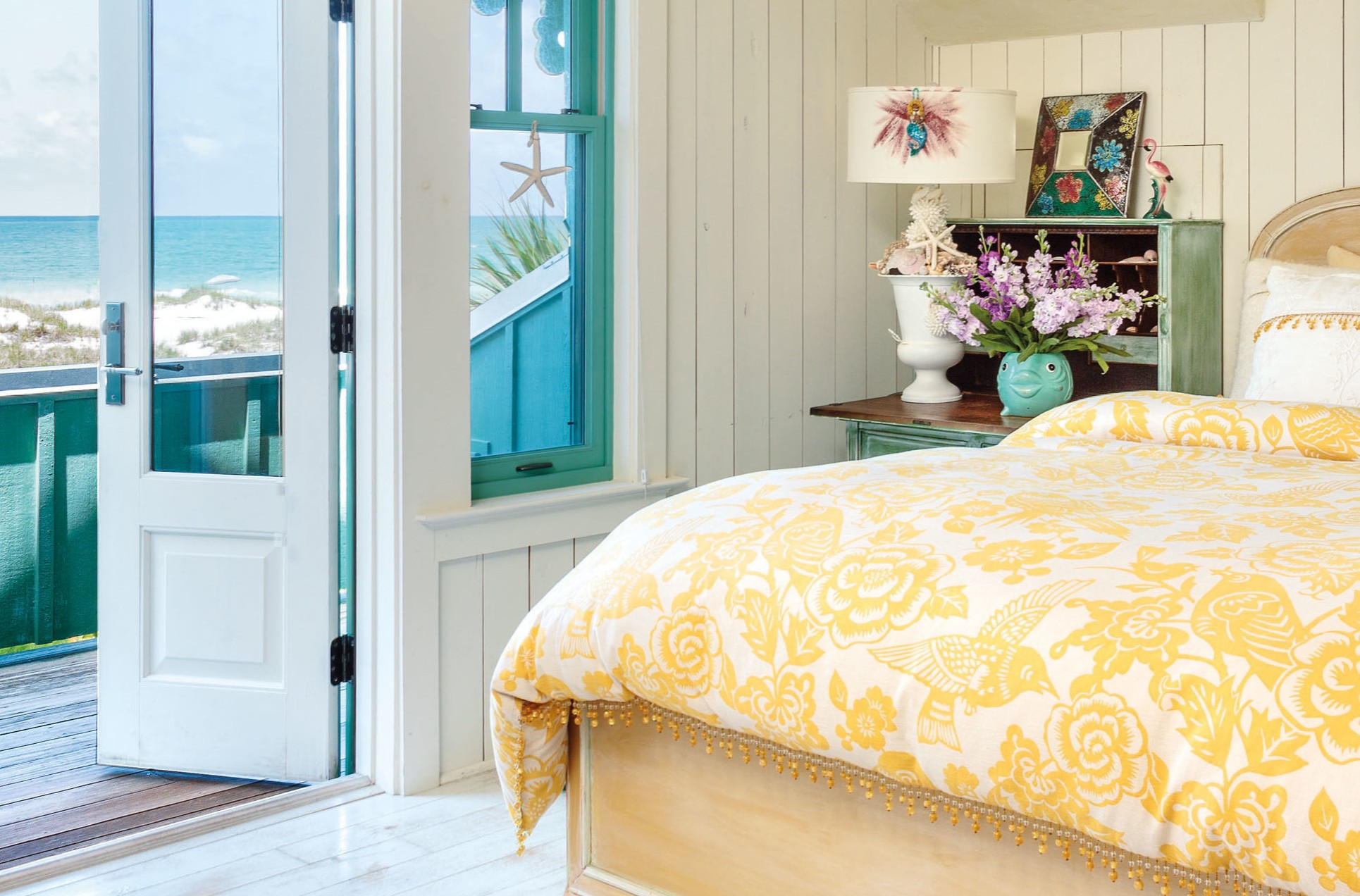 White painted floorboards and pale yellow walls and ceiling create a sunny, shoreside atmosphere, while a fish-shaped vase and a duvet cover decorated with hummingbirds and flowers are the perfect finishing touches. Mark Lohman/Global Bohemian/Cico Books/